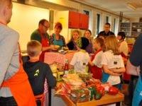 underviser på Fars køkkenskole Jens Augustesen og Minna Elisabeth Pedersen med rødt og blåt forklæde sammen med resten af holdet.